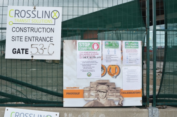 signs re covid-19 on a green fence around a construction site