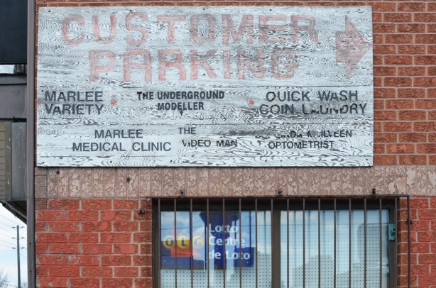 old sign on the side of brick store that says customer parking in faded red letters and then it lists the stores in that plaza