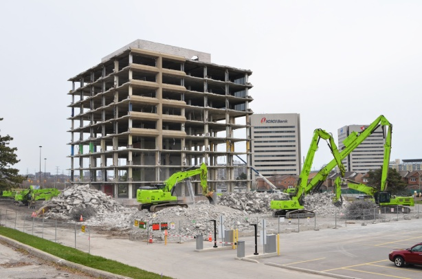 green machery demolishing a parking structure that is now just piles of rubble, beside another building that is partially demolished