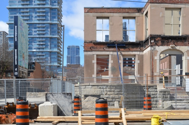 partial demolition of an old house on Jarvis street, facade is left standing, no glass in the windows, can see other high rise downtown buildings through the window holes