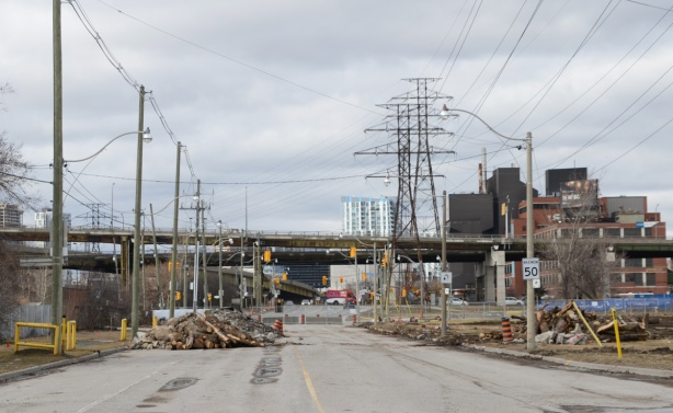 looking north on the closed portion of the Don Roadway, lumber pile in middle of road, large metal hydro poles,