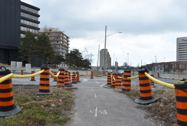 line of orange and black traffic cones on both sides of the sidewalk along Eglinton through Crosstown construction zone