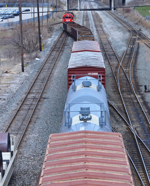seen from a bridge, a train passes below, engine, flatbed cars, a tanker, and a boxcar