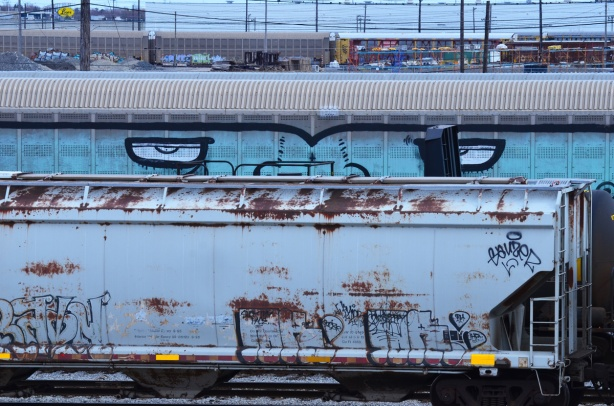 graffiti on the side of a train car - painted pale blue with two big eyes that seem to be looking at the viewer