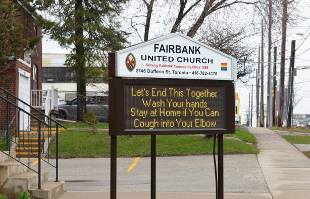 sign outside Fairbank United Church, in lights, that says Let's end this together, Wash your hands. Stay at home if you can. Cough into your elbow.