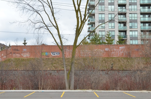 edge of parking lot that it empty, with railway tracks behind, a wall with graffiti, and an apartment building in the background