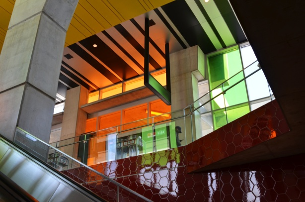 escalator and levels of Finch west subway station, lots of coloured panes of glass, greens, and oranges,