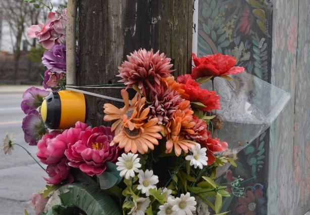 a bunch of fake flowers tied to a pole at an intersection, beside a metal box that has been painted with flowers