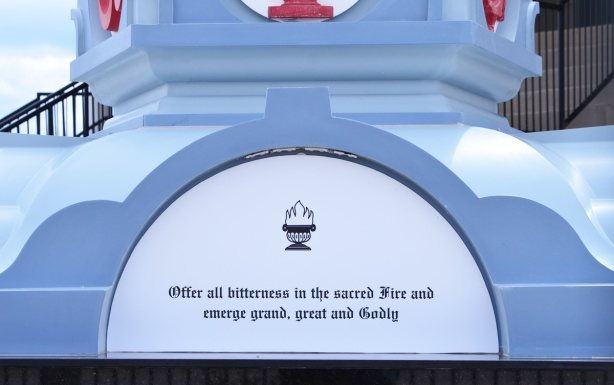 part of the base of a column with words that say offer all bitterness in the sacred fire and emerge grand, great and godly