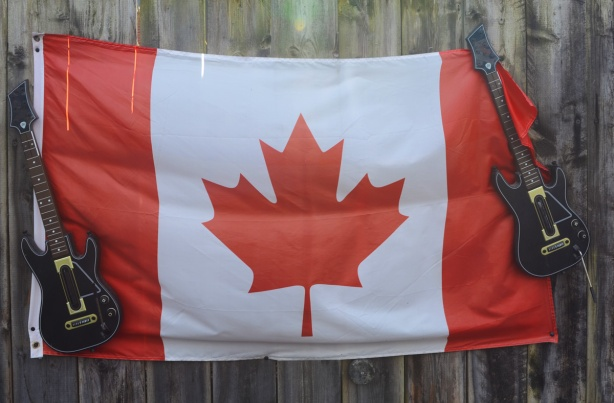 Canadian flag displayed on a fence with a guitar at either end