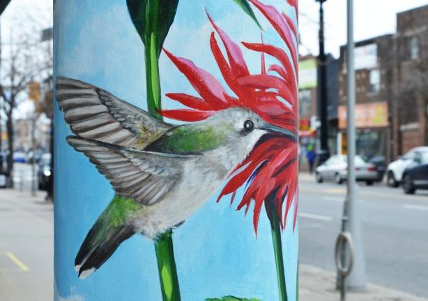 street art of a hummingbird on a pillar, with red flower