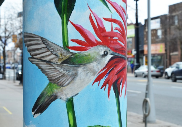 street art of a hummingbird on a pillar, with red flower