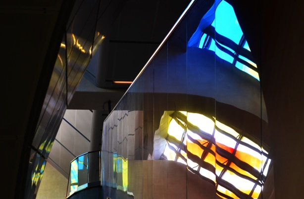 light coming through coloured glass and bouncing colours off walls and reflective surfaces inside subway station