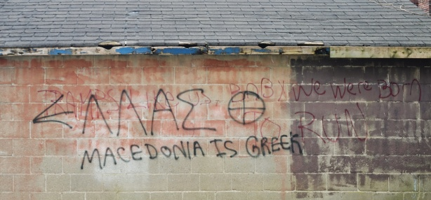 Words scrawled on the side of a concrete block garage in an alley that say Macedonia is Greek