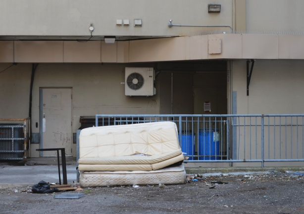 two mattresses discard in a lane beside a blue railing