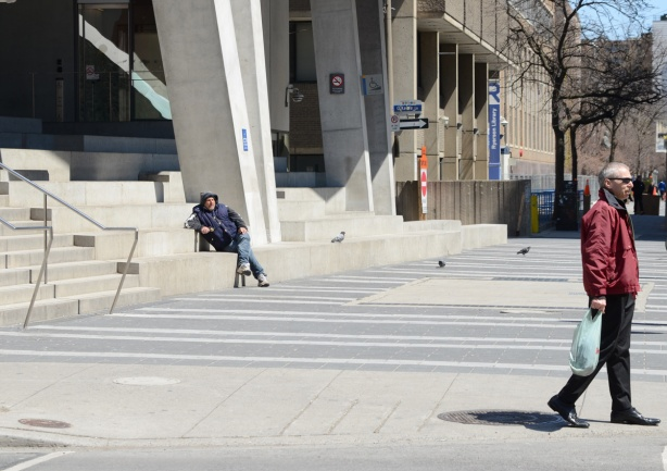 a man sits on the stairs in front of the Ryerson Student Union building while another man walks past