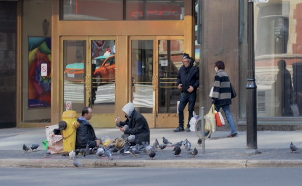 two men sitting on the sidewalk feeding pigeons, many pigeons, a security guard stands by a door behind them and a woman with a face mask walks past