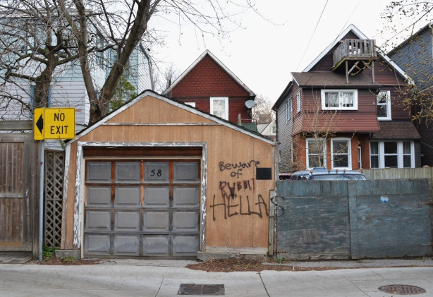 backs of houses and a garage in an alley, graffiti on garage says beware of rabbits