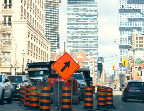 orange and black traffic cones and a lane closed, orange sign with black arrow telling traffic to move to the right