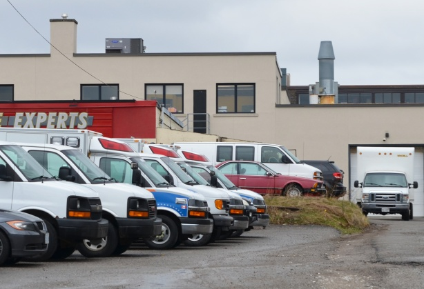 a row of parked cars, light trucks, and ambulances behind an auto mechanic shop