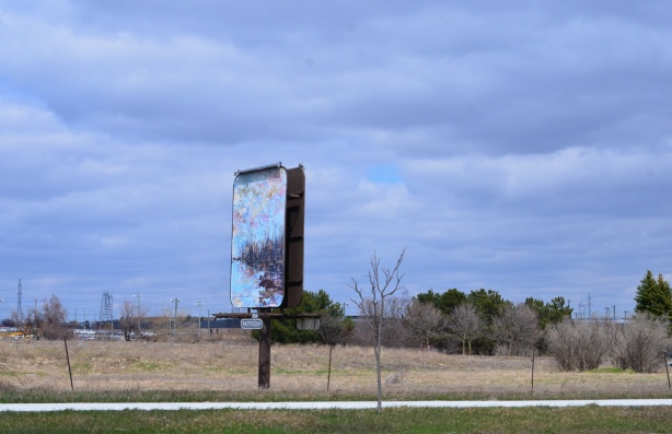pattison billboard beside a street, on a vacant piece of land