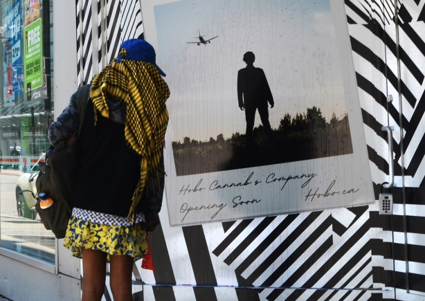 a woman in a yellow and black striped scarf stops to look at a picture on a wall decorated with many black and white stripes going in many different directions, on the stripes is an enlargement of a polaroid picture of a man standing in a field with an airplane flying over him