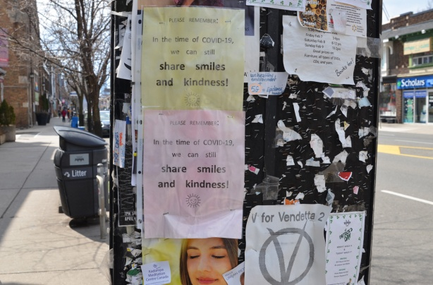 posters on a sidewalk bulletin board,