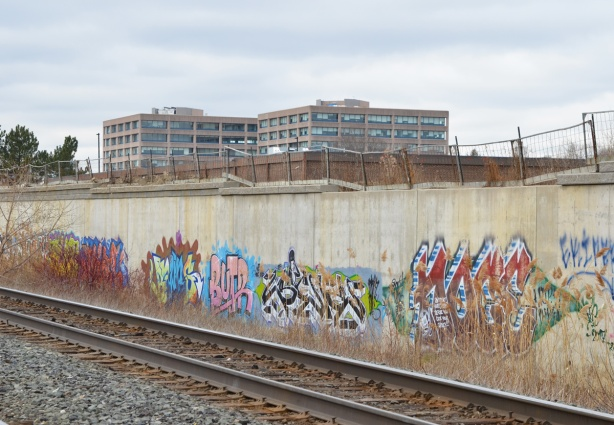 graffiti, tags, along the concrete embankment beside the CPR tracks, apartment buldings can be seen over the wall