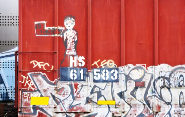 the graffiti on the side of a red boxcar