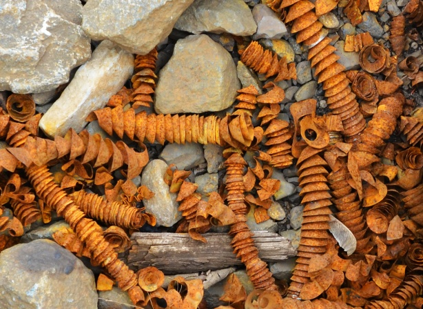 a pile of rusted spiral pieces of metal formed from drilling into the sides of railway tracks, lying in the gravel beside the tracks