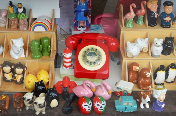 looking in a store window, bright red rotary phone and a display of different types of salt and pepper shakers in differernt shapes - flamingoes, monkeys,