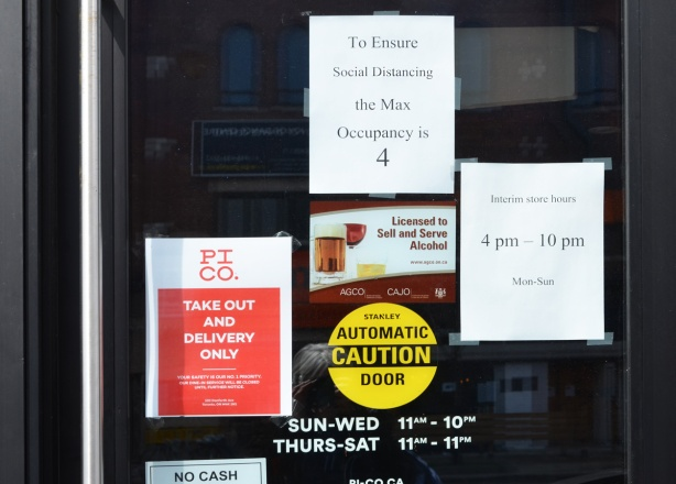 signs and posters on a glass door, entrance to restaurant