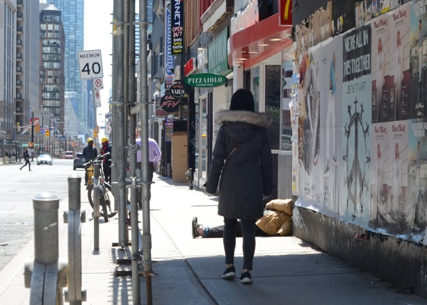 a woman walks down Yonge Street under a covered walkway (for construction) and towards a man half sitting and half lying on the sidewalk, with one leg stuck out into the sidewalk