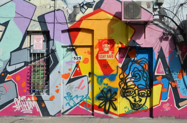 wall and doors to numbers 533 and 535 covered with street art including an urabn ninja squadron character with a face mask on with the words stay safe