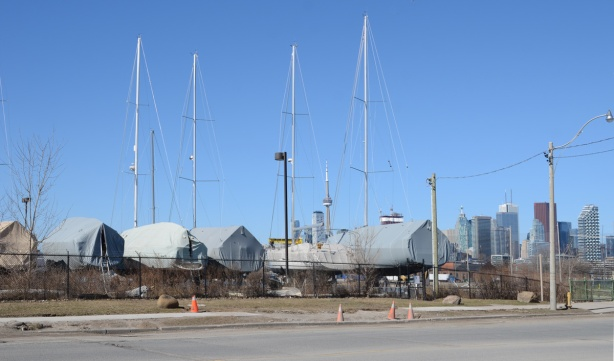 a line of large sail boats in storage, on land, covered with tarps, masts in the air, no sails,