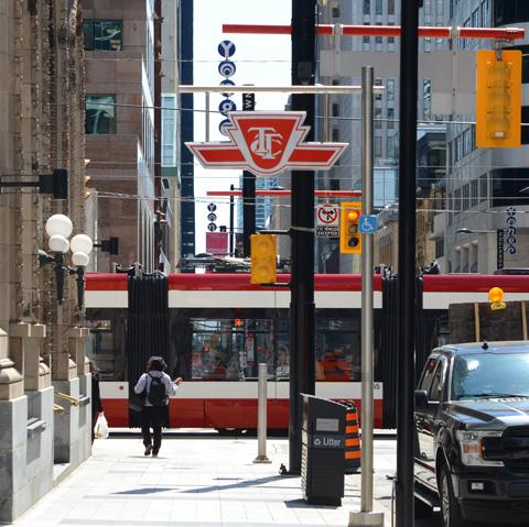 a woman walks towards the side of a TTC streetcar as it crosses over Yonge Street