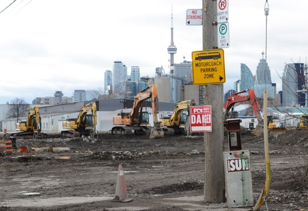 construction, signs on a wood pole, Toronto skyline in the background