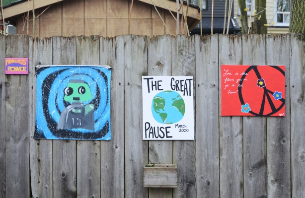 paintings on a fence including one that says the great pause.