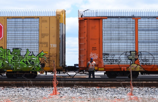 a man in a safety vest stands beside two boxcars, one yellow and the other orange,