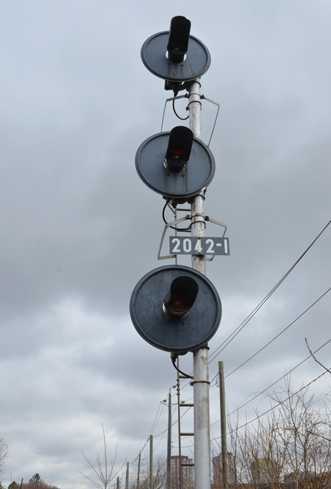 a set of three railway lights at 2042-1 pole, lights are arranged vertically, one on top of the other