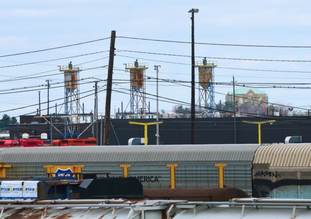 three tanks on towers above train cars at CPR yard