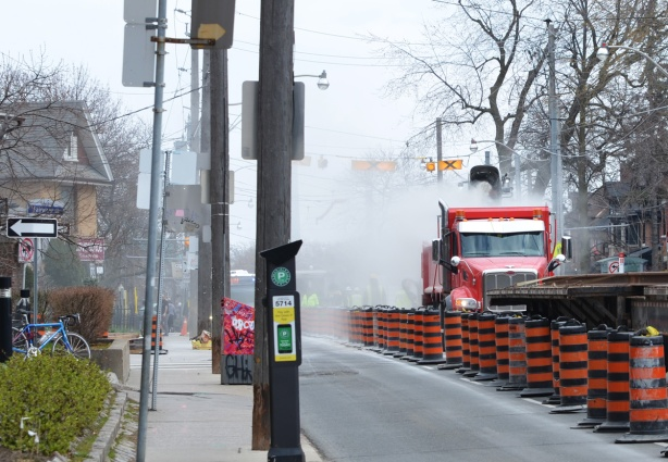 a red truck in the middle of Broadview Ave as TTC streetcar tracks are being removed, lots of dust.