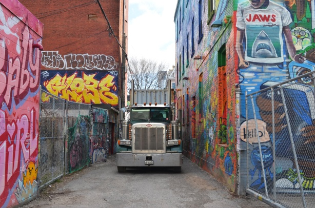 a large semi truck is parked in Graffiti Alley and is taking up the whole width of the lane