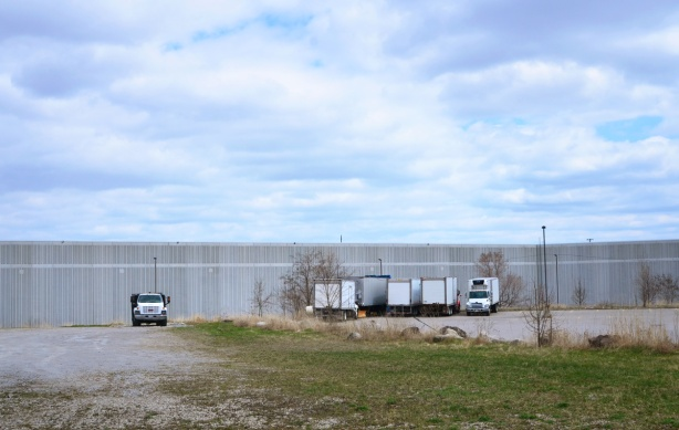 trucks parked beside a long low grey building, in the distance. in front is a vacant lot
