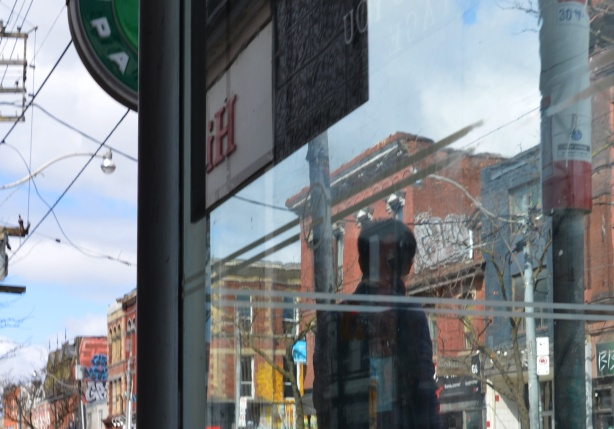 a person waiting beside a bus shelter on Queen West, seen from the back including reflections in the glass of the shelter
