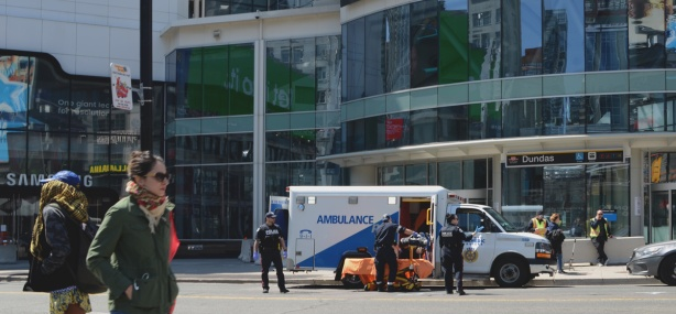 ambulance with paramedics talking to a man who is sitting in the ambulance, at Yonge and Dundas in front of the Easton Centre