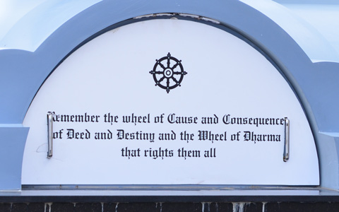 part of the base of a column with words that say remember the wheel of cause and consequence of deed and destiny and the wheel of dharma that rights them all