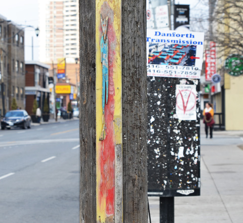 long narrow shapes made of wood and painted blue an red and attached to wood utility pole