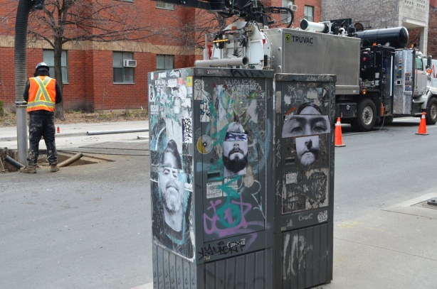 paper paste up graffiti of faces and eyes by Jeremy Lynch on metal boxes on the sidewalk, with construction workmen in the background