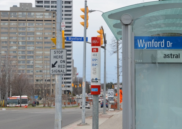 bus stop and shelter on Don Mills Road at Wynford, Crosstown construction and high rises in the background